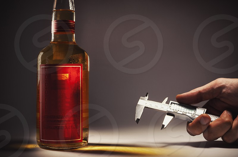 Alcohol drink in a bottle and hand with micro measure tool.  photo