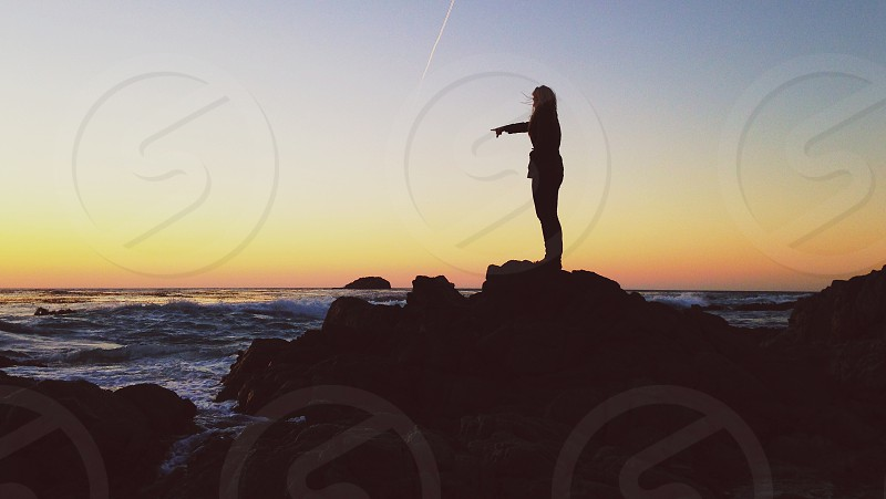woman in rock standing on beach photo