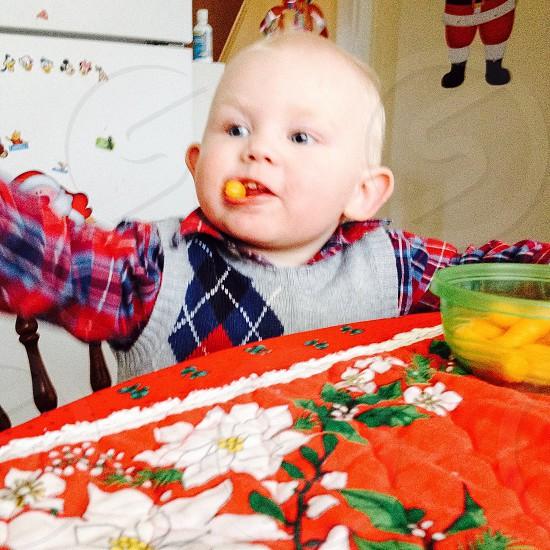 Cute little man eating cheesies photo