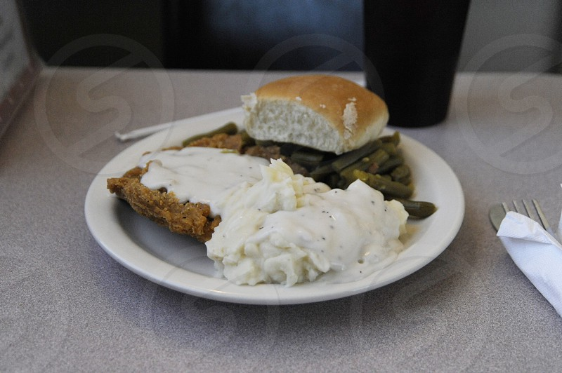Chicken fried steak dinner with roll mashed potatoes and gravy and green beans photo