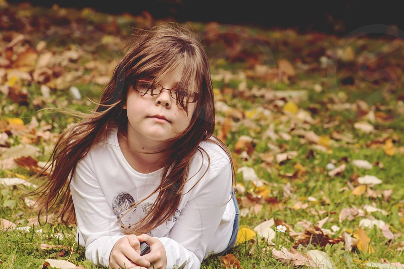 focus photography of girl wearing eyeglasses with white crew neck printed long sleeve shirt laying on the green grass with brown falling leafs on grown and a windy air photo