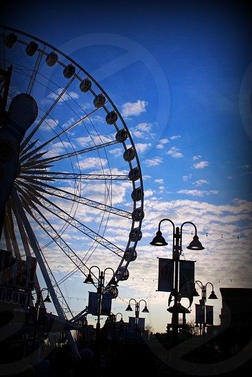 silhouette of ferry's wheel and pedestal lamps under white cloud blue skies photo