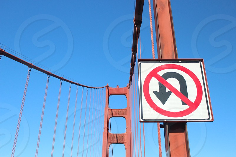 Golden Gate Bridge against a clear blue sky with a closeup of a NO U TURN sign. photo