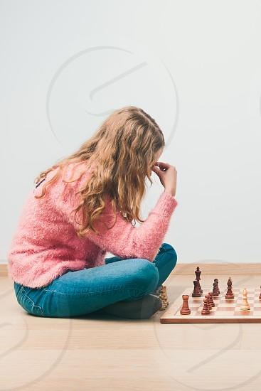 Girl deeply thinking about next move during chess game. Copy space for text at the top and bottom of image photo
