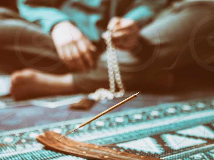 Concentrated woman praying with wooden rosary mala beads. Close up focus on incense stick. Retro vintage filter. photo