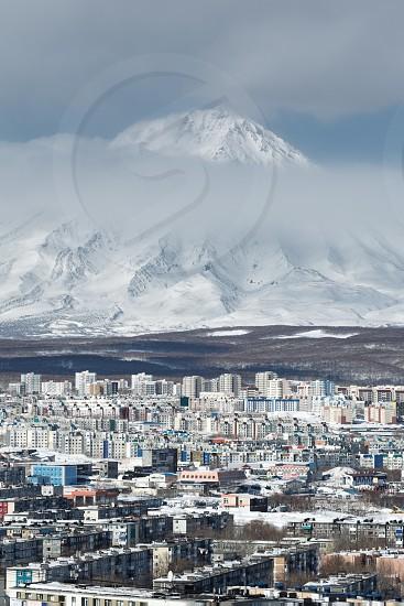 Winter cityscape: top view of Petropavlovsk-Kamchatsky City and active Koryak Volcano on a cloudy day. Far East Russia Kamchatka Peninsula. photo