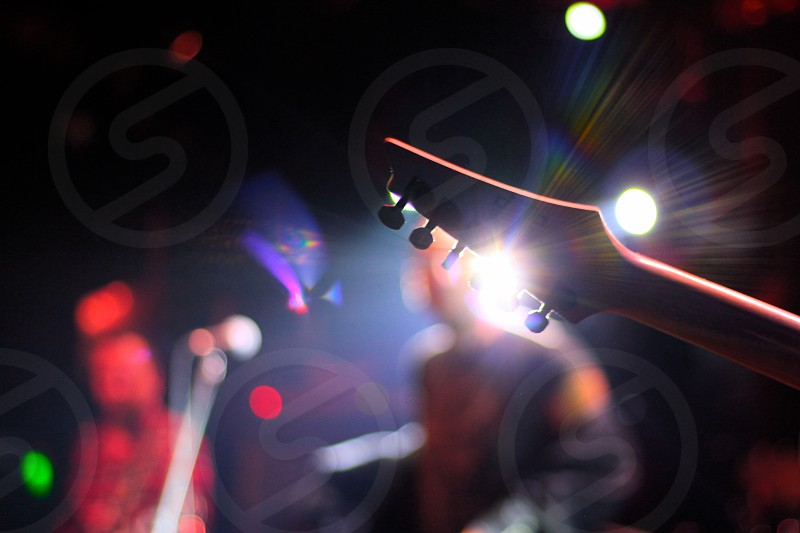 brown electric guitar headstock near band playing on concert stage photo