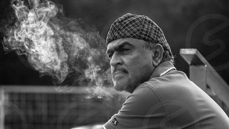 man in grey collared shirt smoking photo