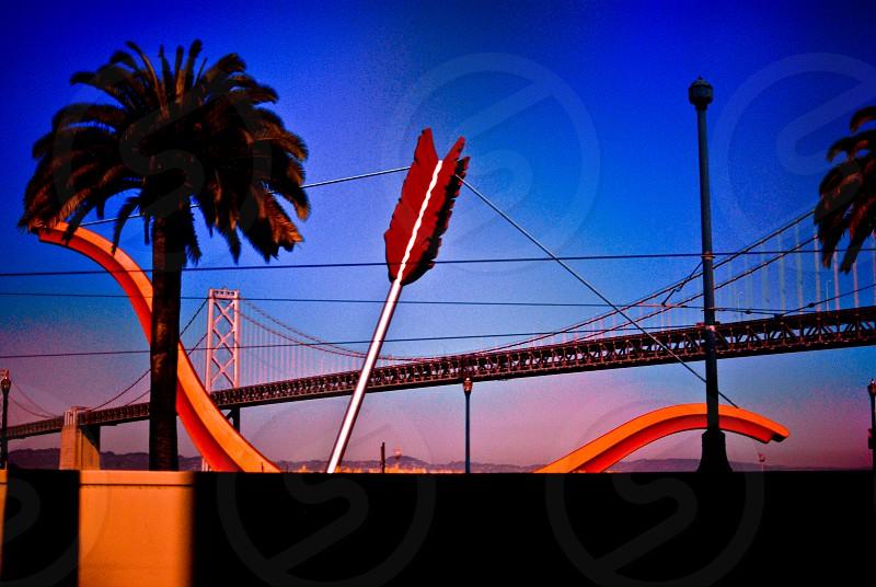 red and orange arrow illustration and bridge background photo
