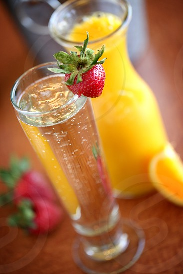 Summer themed cocktail with a strawberry placed in front of a carafe of orange juice. photo