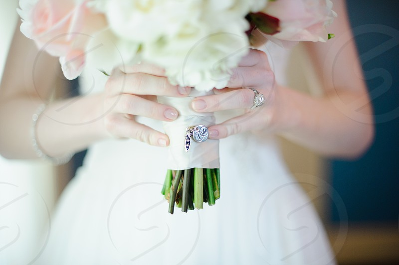 Bride holding flower bouquet with charm saying I do photo