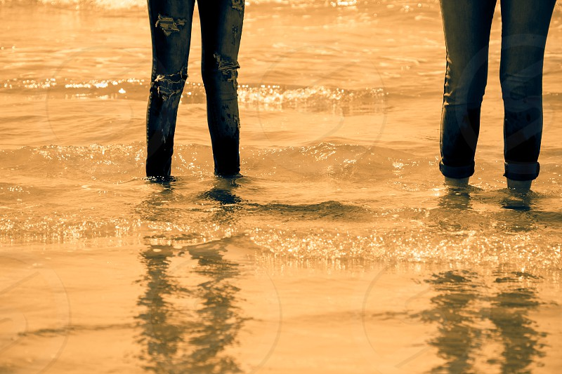 Women legs in blue jeans standing in the sea water on the coast - golden tone. photo