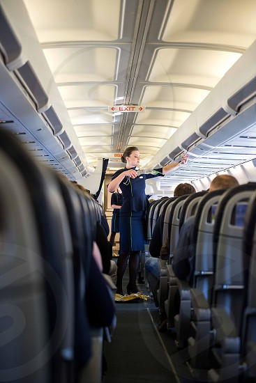 Riga Latvia - April 03 2019: Stewardesses in the cabin of the passenger airplane instructs passengers on safety measures in the event of an emergency before the flight from Riga (RIX) to Zurich (Kloten) (ZRH) photo