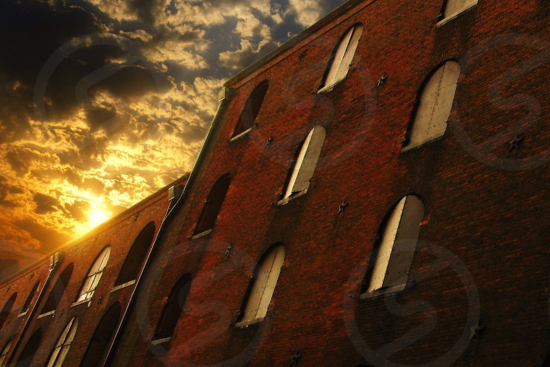 low angle photo of brown brick framed building under cloudy sky on day time photo