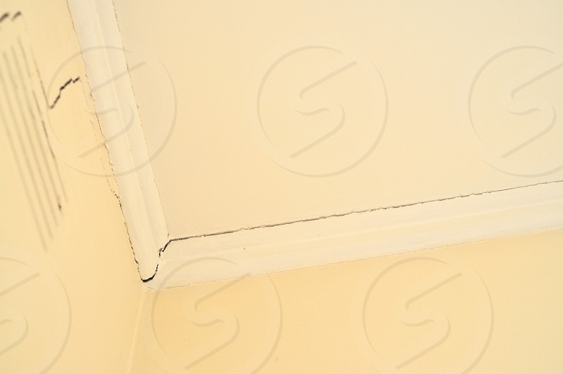 Cracks in the corner of a room with yellow walls and filled with natural light    photo