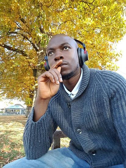 Man thinking park headphonesblack man cardigan grey  photo
