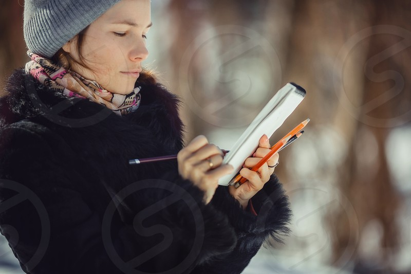 Young woman outdoor portrait with sketchbook and pencils. Pencil drawing draw sketch portrait spring winter person education look book painting artists painted business coat charcoal pastel photo
