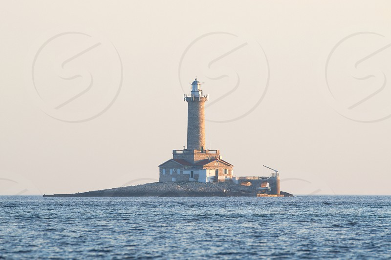 Lighthouse Porer against Clear Summer Day Sky at Sunset in Kamenjak Croatia photo
