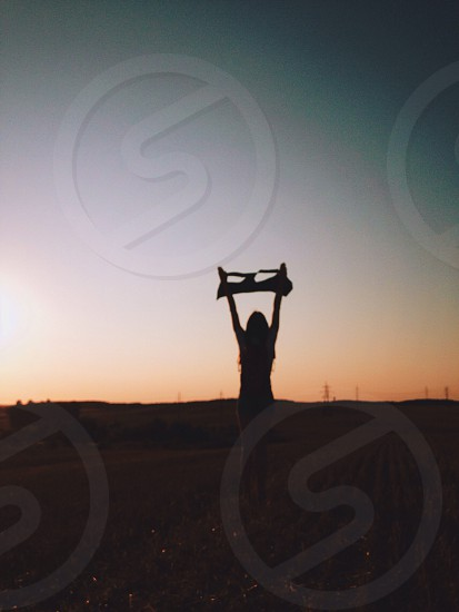 silhouette of woman lifting textile photo