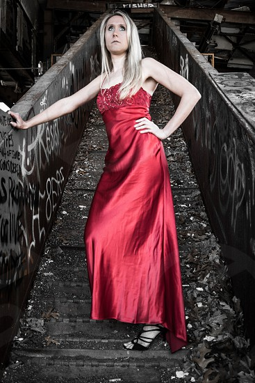 Beautiful woman in red dress posed inside a warehouse with grit and graffiti. Colorful grungy  young woman photo