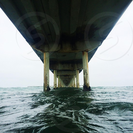 water with pier and yellow pylons photo