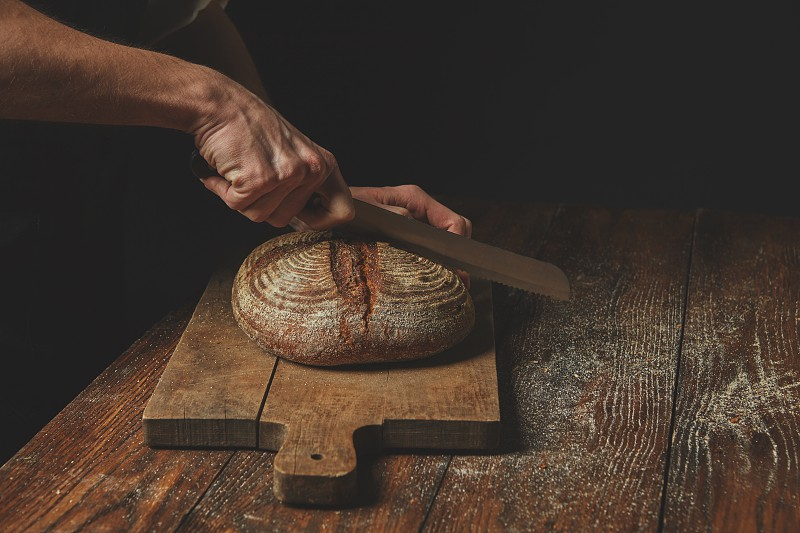 Men's hands cut round rye bread on a wooden brown cutting board photo
