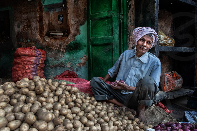 agra; agriculture; asian; city; color; colorful; composition; dress; food; fresh; green; grocer; grocery; horizontal; india; indian; male; man; market; on; onions; outdoors; pattern; people; person; photography; portraits; potatoes; sack; sale; sell; seller; senior; seniors; shop; sitting; stall; texture; the; tradition; traditional; vegetables; vendor; wall;  photo