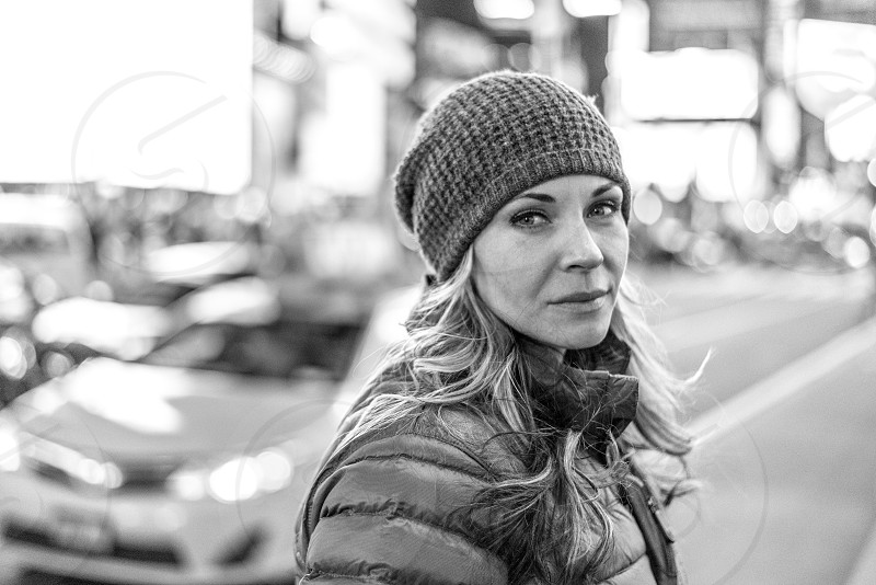 Black and white portrait of an attractive woman looking at the camera in an urban setting. photo