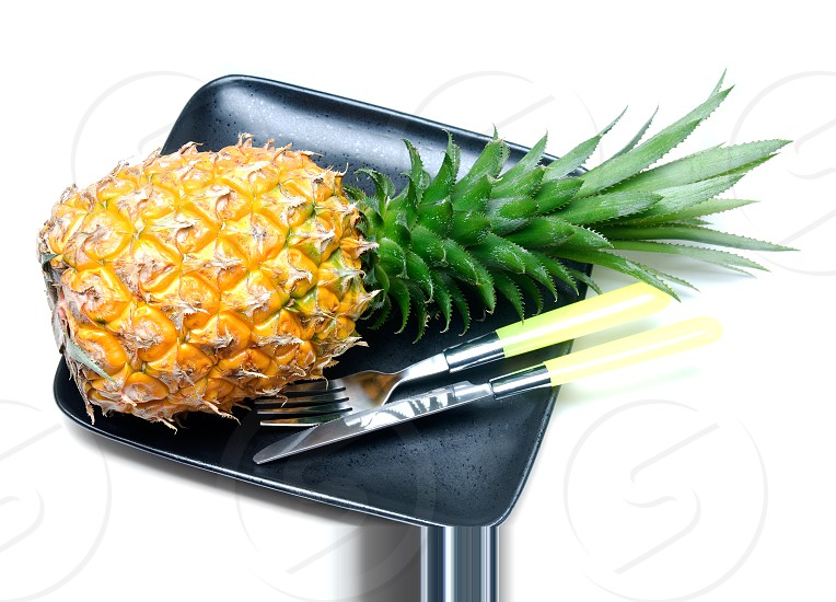 ripe vivid pineapple on a black plate with knife and fork isolated over white photo