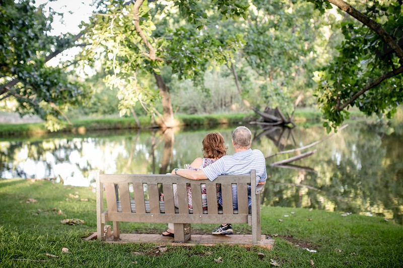 An elderly couple sit together on a bench enjoying the view of a lake on a stunning summer day. photo