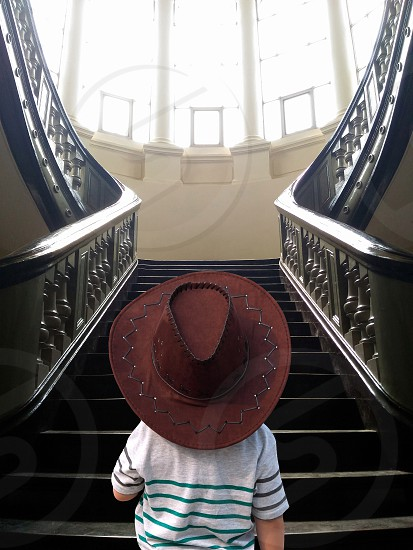 person wearing brown leather cowboy hat in front of black stairway during daytime photo