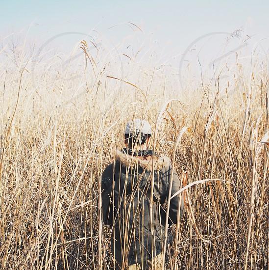 man in black winter jacket walking on tall brown grass field photo