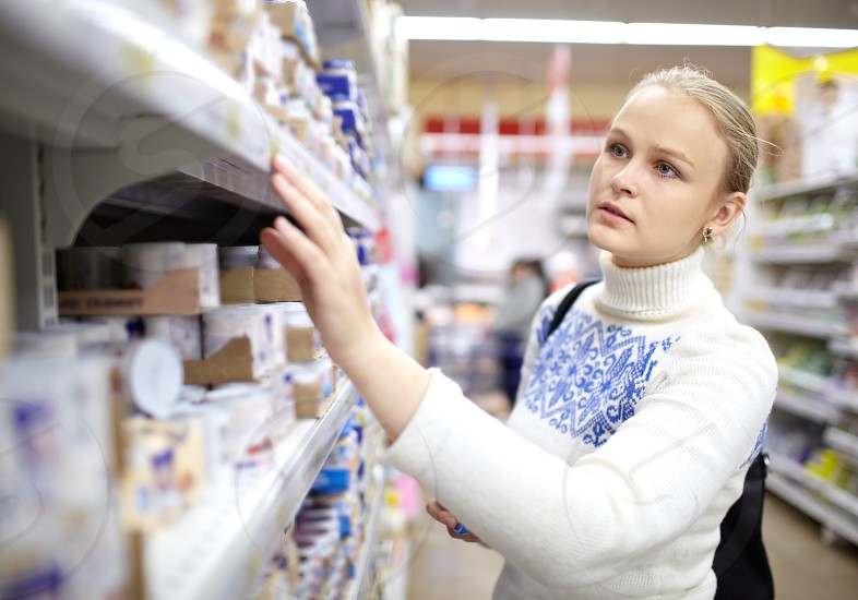 Young woman is choosing food for her child in the supermarket. photo