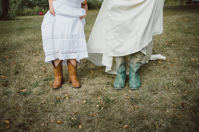 women in white dresses and cowboy boots photo