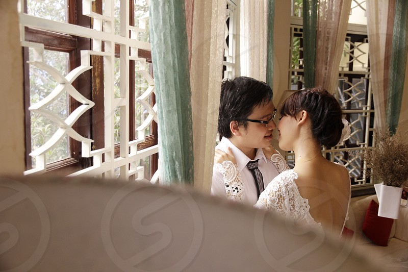 Bride and Groom on pre-wedding photo shooting day. Kissing near the windown. Location: Coffee Shop photo