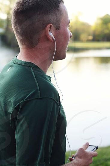 man in green shirt listening to music photo