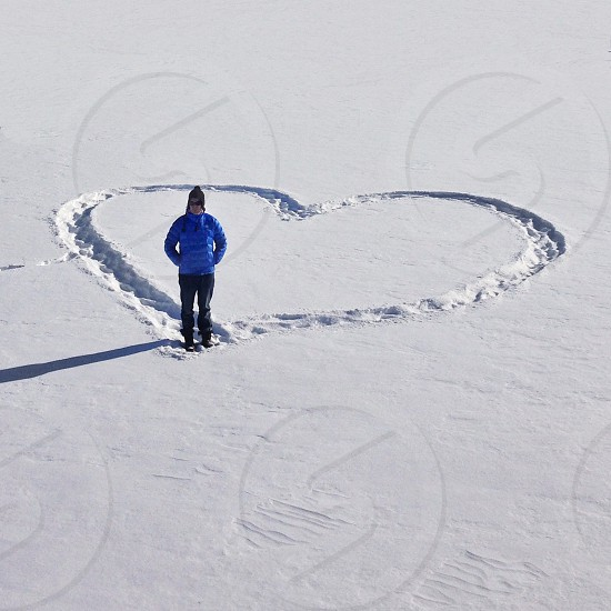 man standing on heart shaped snow photo