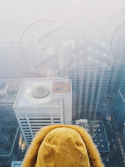 person in tan khaki jacket with fur hood overlooking scenic city aerial view photo