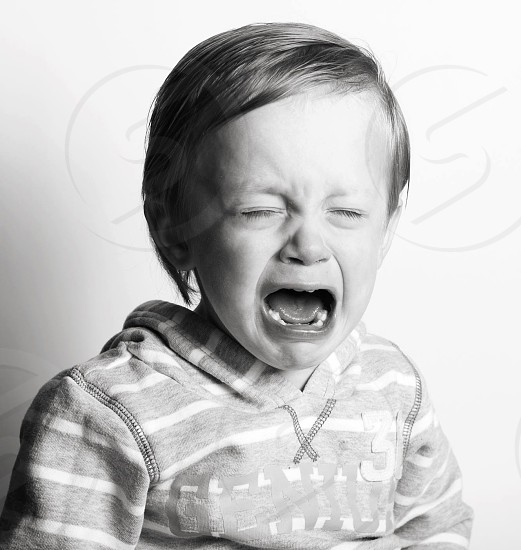 crying boy in grayscale photograph photo