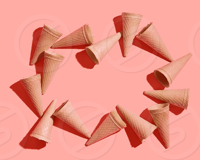Frame from sweet wafer cones for dessert empty on a color background of the year 2019 Living Coral Pantone place for your text. Spring or summer food concept. Top view. photo
