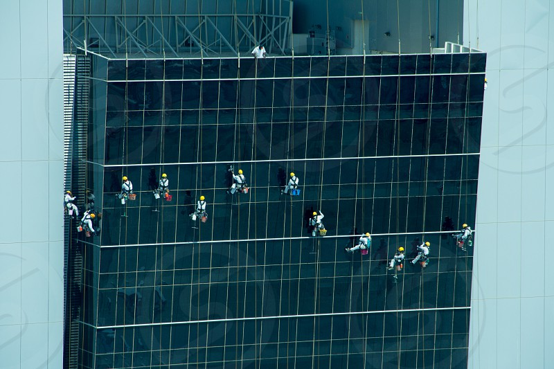 A dozen window cleaners working at 40 stories. photo