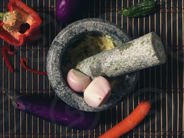 Malaysian food preparation with pestle and mortar garlic ginger capsicum carrot and bitter gourd. photo