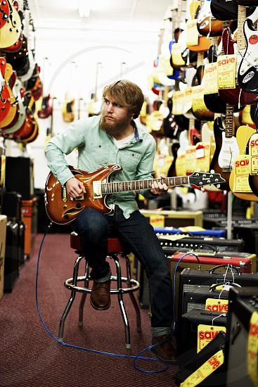 man in blue long sleeved button down shirt playing guitar photo