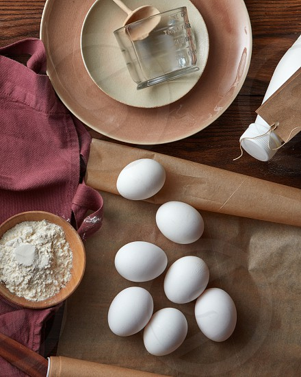 ingredients for pancakes and pies on a wooden table with utensils and baking paper flat lay photo