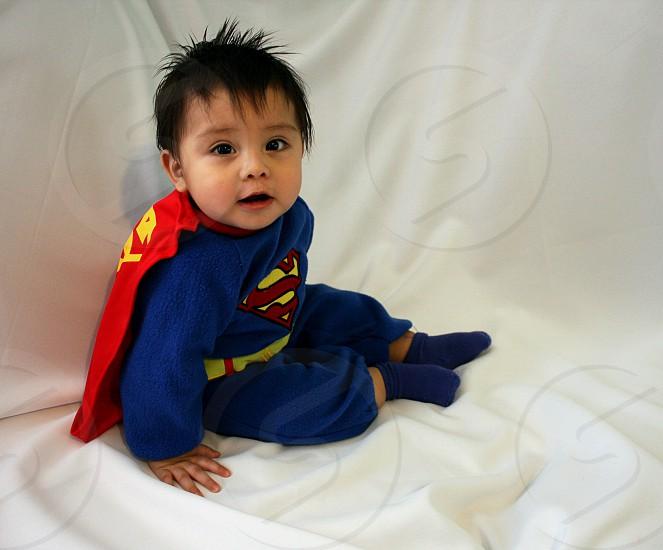 boy wearing super man costume sitting on white textile photo