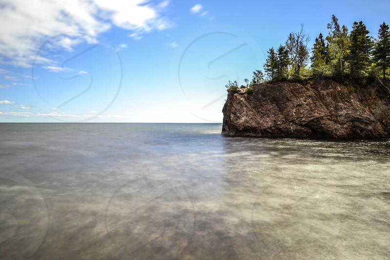 Long exposure of lake with rocky shoreline photo