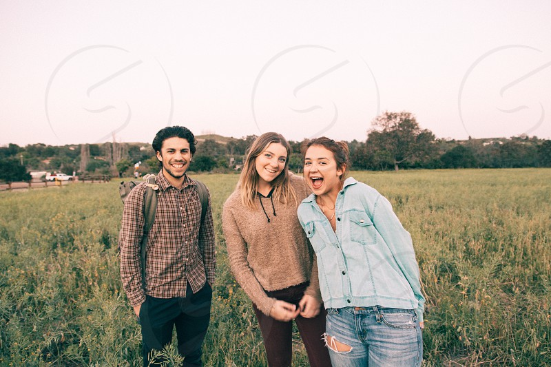 man in brown white checkered dress shirt smiling standing beside 2 girls smiling standing in green grass field at daytime photo