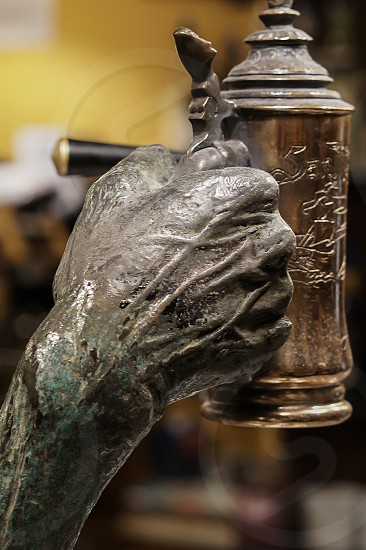 Hand made of stone holding a beer tankard photo