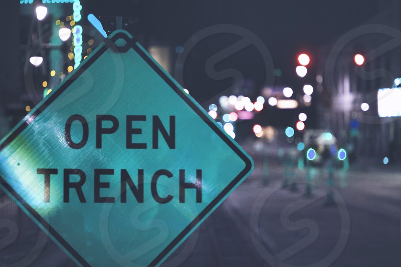 low light selective focus photo of open trench signboard during night time photo