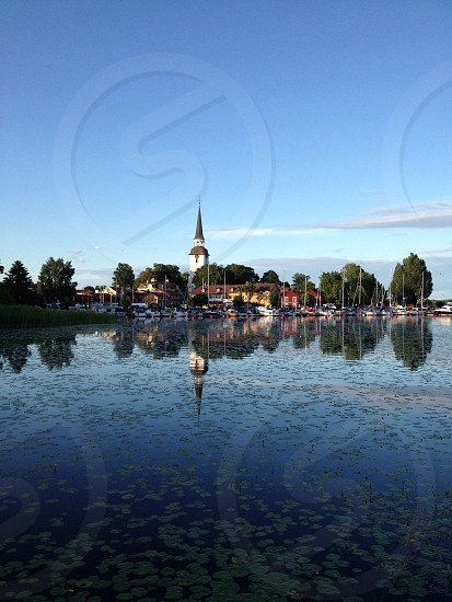 White and brown steeple building across teh lily filled water photo